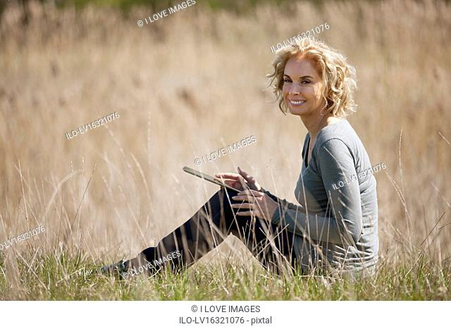 A mature woman sitting in long grass, using a digital tablet
