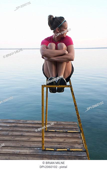 Young Woman Seated On Dock Ladder, Clear Lake, Riding Mountain National Park, Mantioba, Canada
