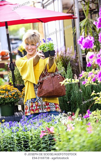 A pretty 42 year old blond woman shopping at a garden store holding a 6 pack of pansies