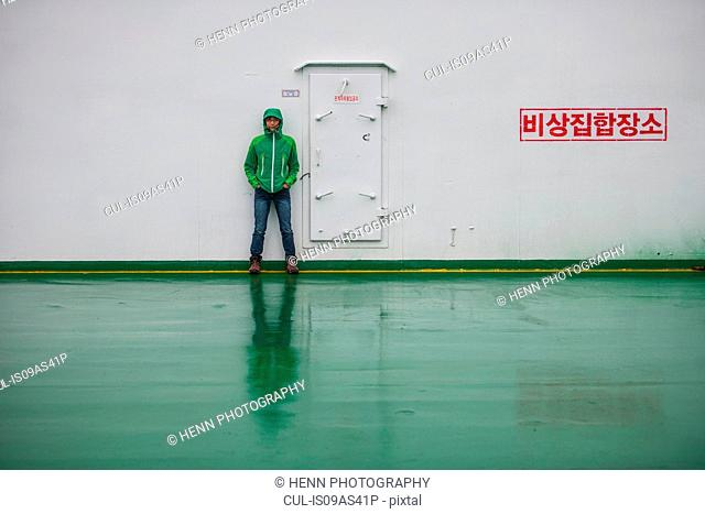 Woman standing next to door on ferry to Jeju Island, South Korea