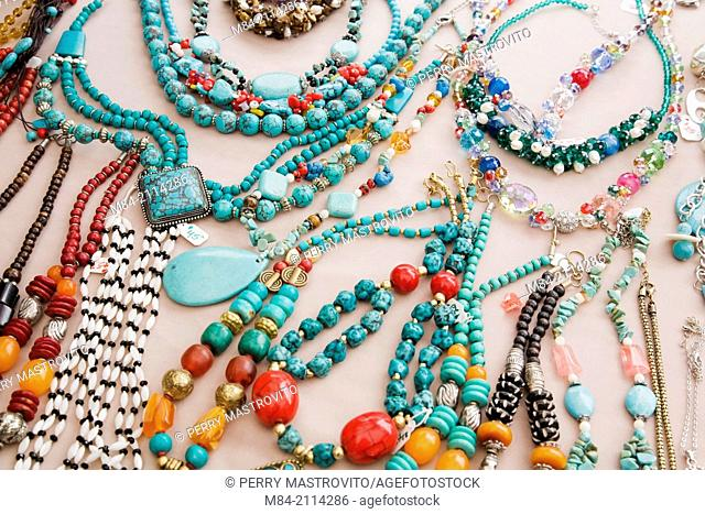 Assorted turquoise necklaces for sale displayed on a gray cloth background at an outdoor market, Byward Market, Ottawa, Ontario, Canada