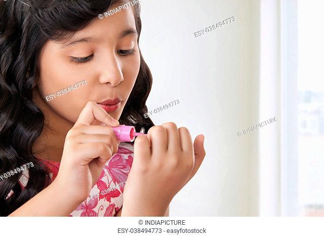 Cute girl applying nail paint