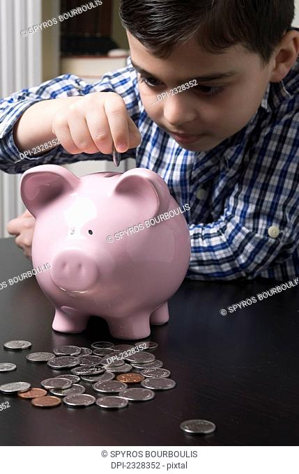 Boy Depositing Coins Into A Piggy Bank; Laval, Quebec, Canada