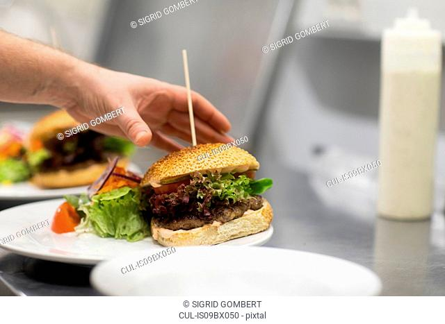 Fast food worker preparing hamburger and salad in commercial kitchen, close up of hand