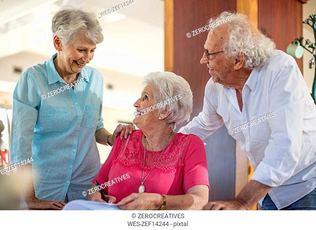 Senior woman signing a contract, friends reassuring her