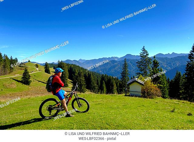 Germany, Mountainbiker looking to Hirschtalsattel, Aueralm with Tegernsee Mountains near Lenggries
