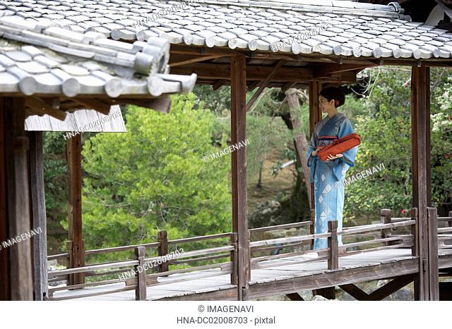 Young Japanese woman in kimono walking on wooden bridge