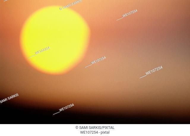 Blurred solar disc at sunrise creating a dramatic sky