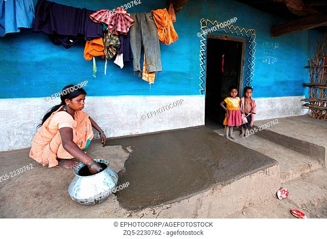 Tribal woman applying cow dung or manure in courtyard, Baiga tribe, Karangra Village, Chhattisgarh, India