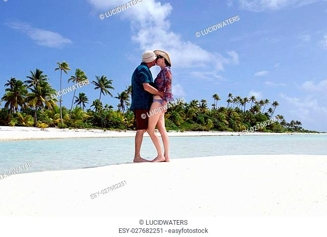 Young couple, male and female kisses on the white sand of a deserted tropical island in Aitutaki Lagoon, Cook Islands