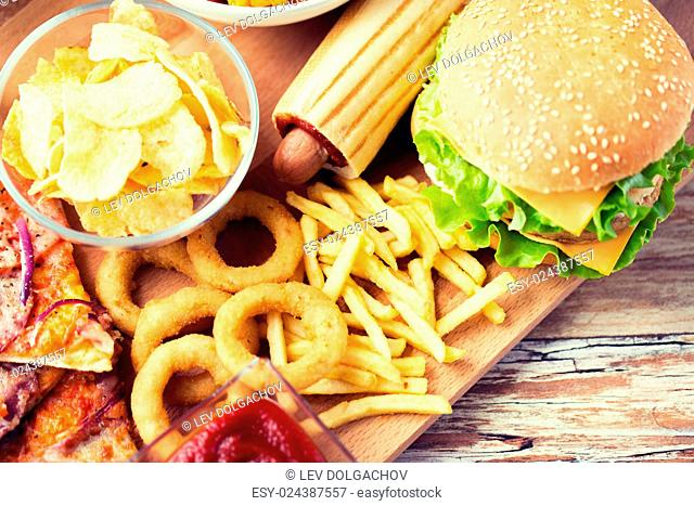 fast food and unhealthy eating concept - close up of hamburger or cheeseburger, deep-fried squid rings, french fries hotdog and potato chips on wooden table top...