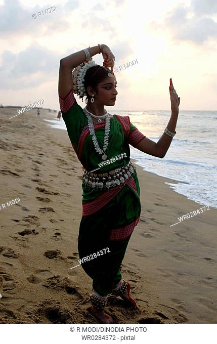 Dancer performing classical traditional odissi dance in front of bay of Bengal sea , Konarak , Orissa , India MR 736D