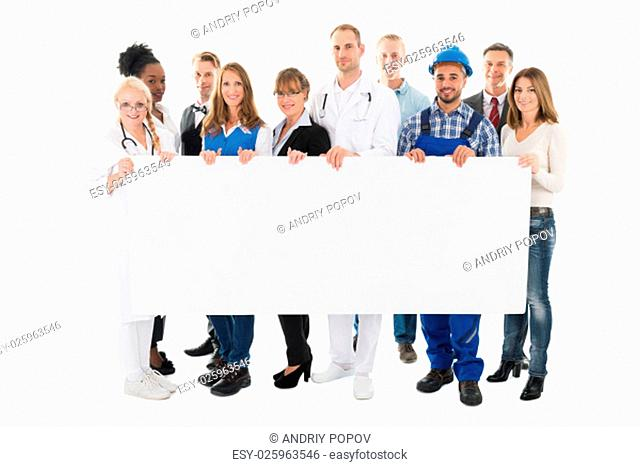 Group portrait of people with various occupations holding blank billboard against white background