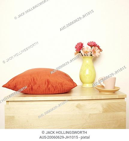 Close-up of a flower vase and a cushion with a cup on the table