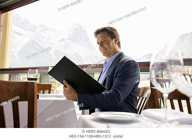 Businessman reading menu at table on balcony
