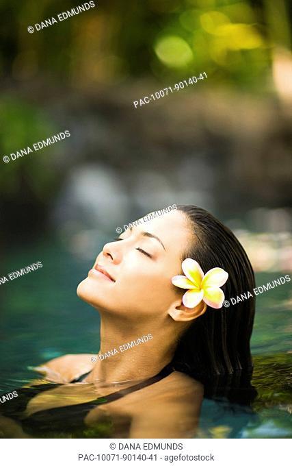 Hawaii, Oahu, Closeup of young woman's face relaxing in tropical pool