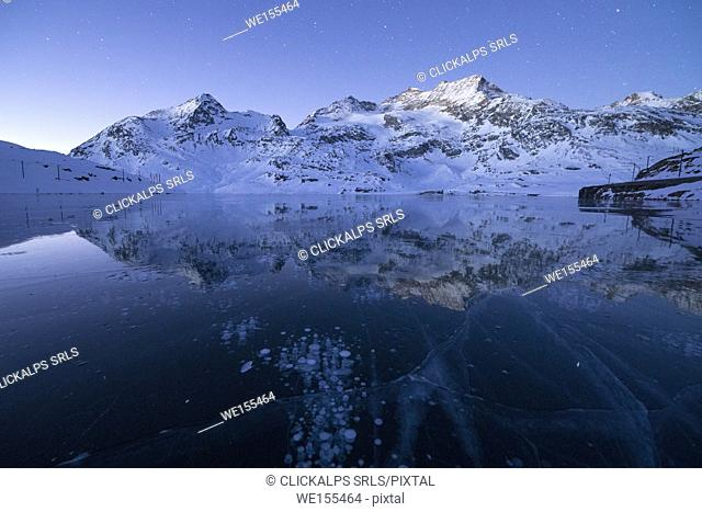 Ice bubbles frame the snowy peaks reflected in Lago Bianco Bernina Pass canton of Graubünden Engadine Switzerland Europe