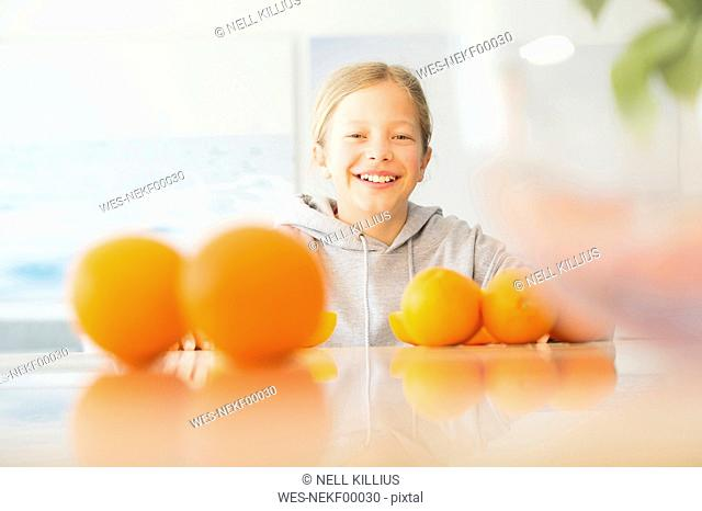 Portrait of happy girl with oranges in kitchen