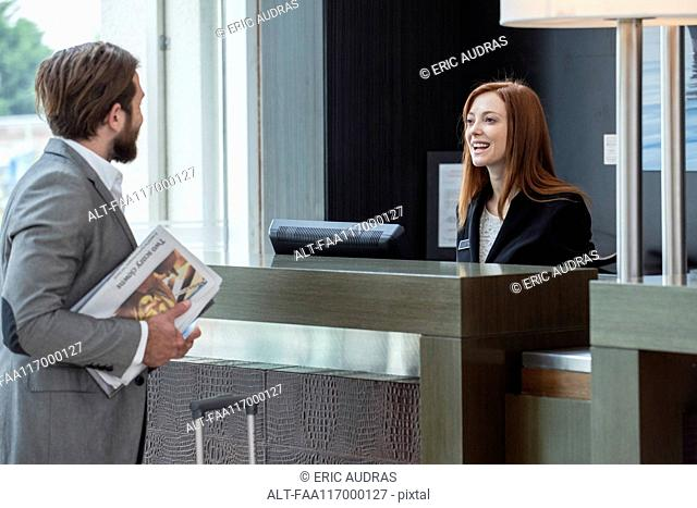 Businessman talking with female receptionist