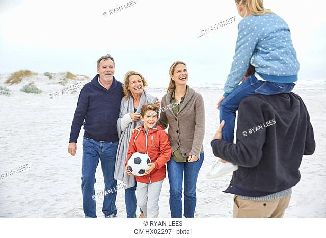 Multi-generation family with soccer ball on winter beach