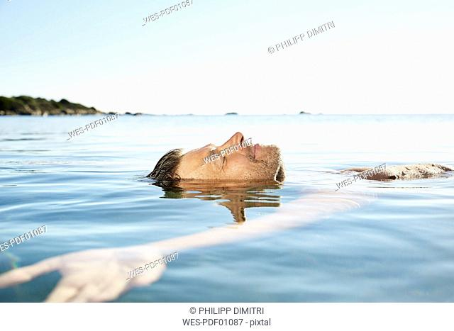 Relaxed mature man floating in the sea