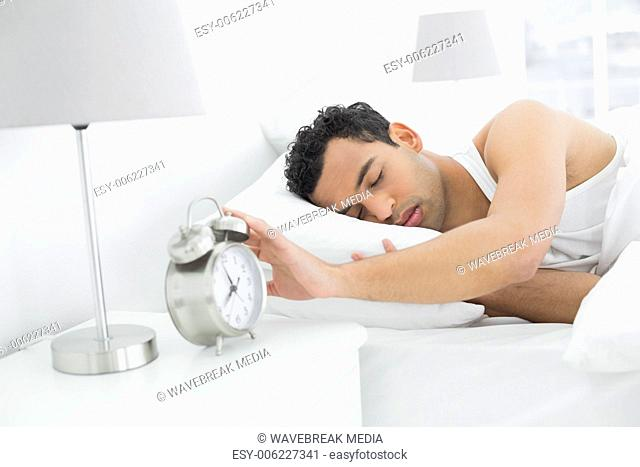 Sleepy man extending hand to alarm clock