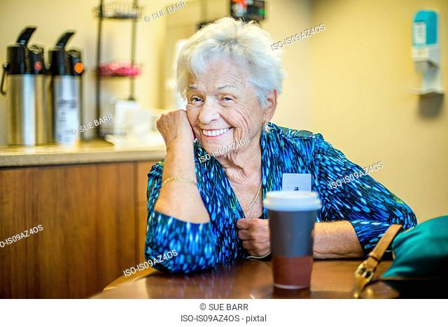 Gray haired woman at table looking at camera smiling