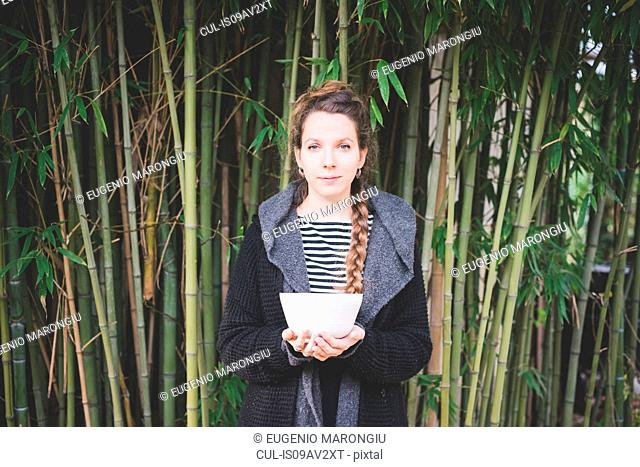 Front view of young woman standing in front of bamboo grove holding ceramic dish looking at camera