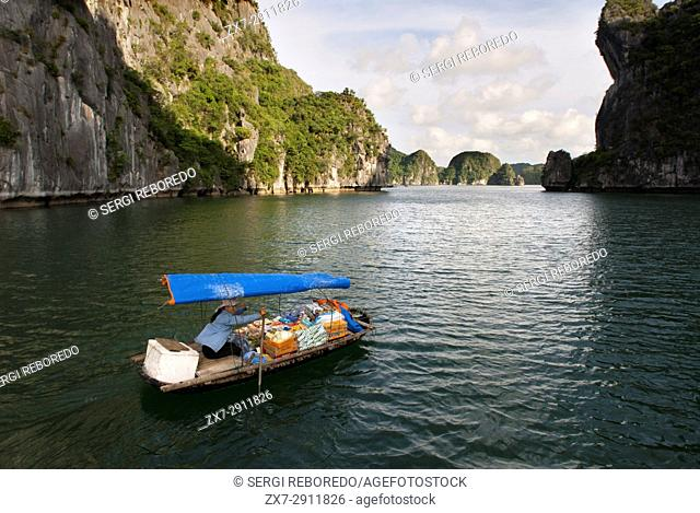Boat woman vendor in Halong Bay, Vietnam. Drink snack hat vendor rowing boat Halong Bay Vietnam