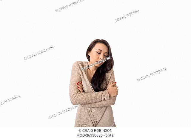 Young woman with arms crossed shivering against gray background