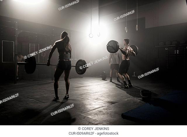 Man and woman lifting barbells in gym, rear view