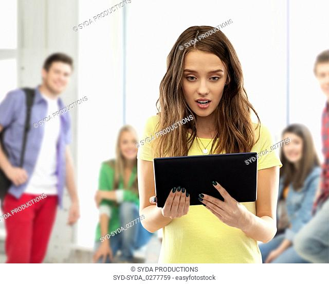 shocked student girl with tablet pc at school