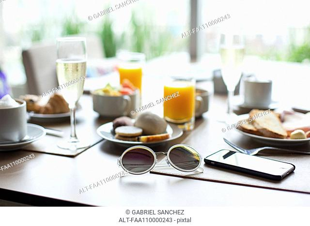 Sunglasses and breakfast on table in cafe