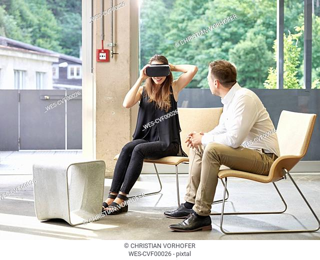 Man looking at woman wearing VR glasses sitting on chair