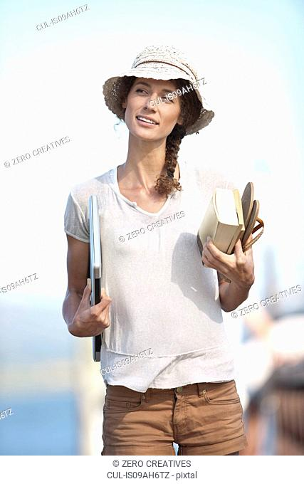 Portrait of young woman holding book, sandals and laptop