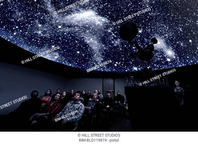 Students watching constellations in planetarium