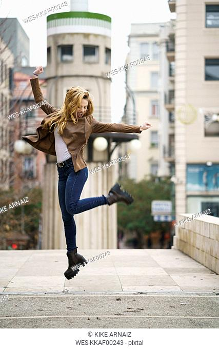 Excited young woman jumping in the air