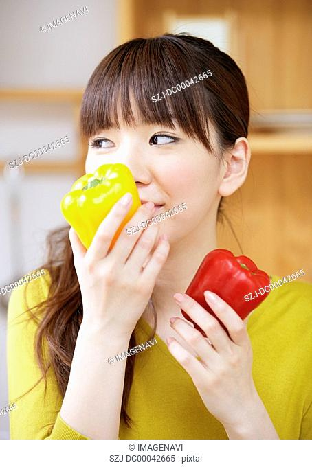 Young woman holding a bell pepper
