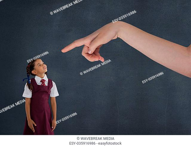 Hand pointing at girl looking up against blue background