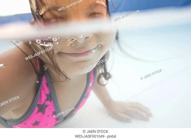 Little girl diving underwater in a paddling pool