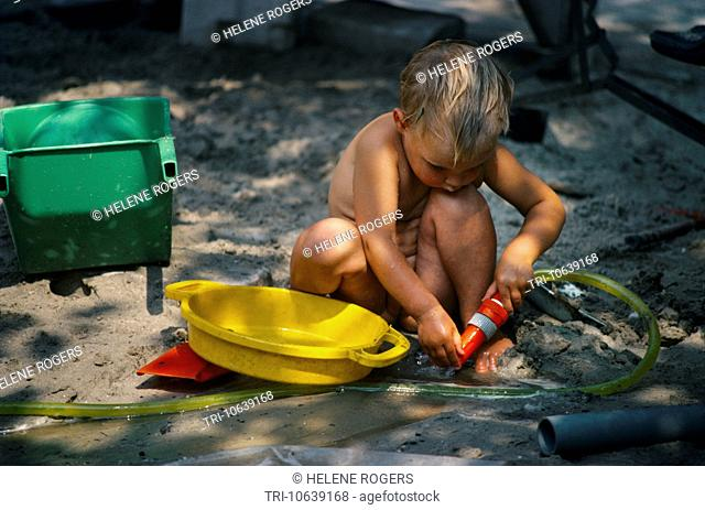 Amsterdam Holland Vondelpark A Young Girl Playing In A Sand Pit With A Hose At An Outdoor Creche