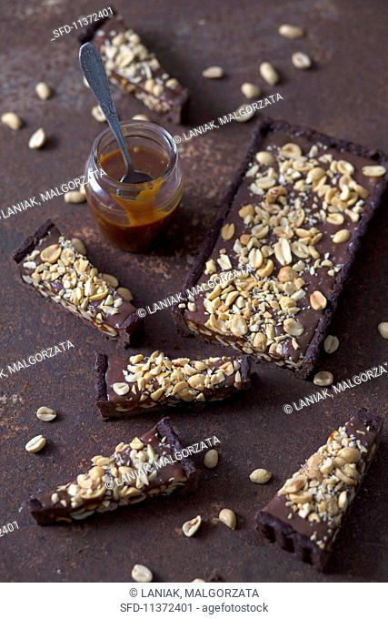 Slices of chocolate tart with peanuts and homemade caramel sauce