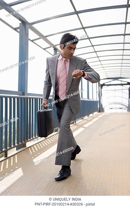 Businessman checking the time on a footbridge, Gurgaon, Haryana, India