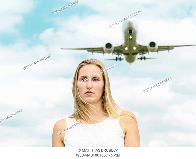 Flying plane behind young woman in white dress