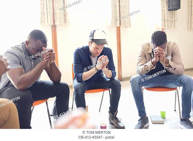Men praying with rosaries in prayer group