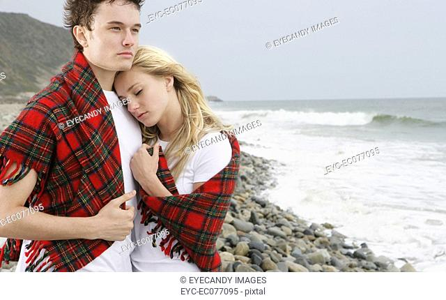 Portrait of young couple with blanket standing on pebbled beach