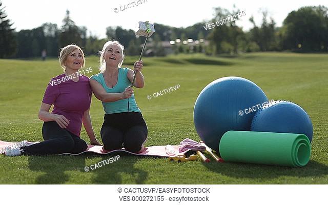 Smiling fitness senior women taking selfie in park