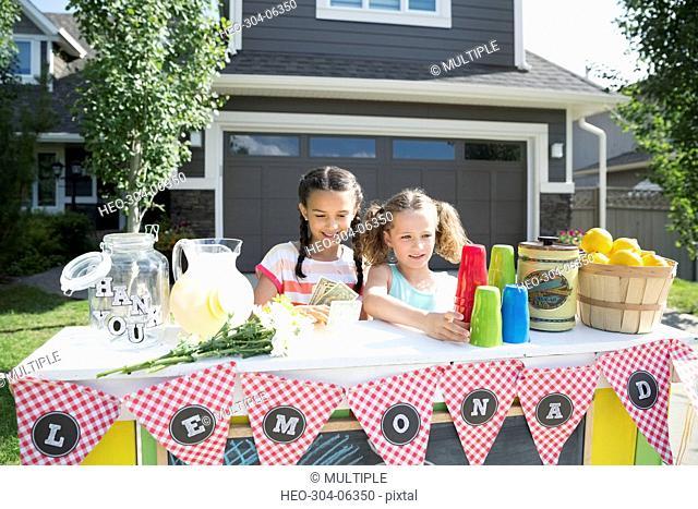 Girls preparing lemonade stand in sunny driveway