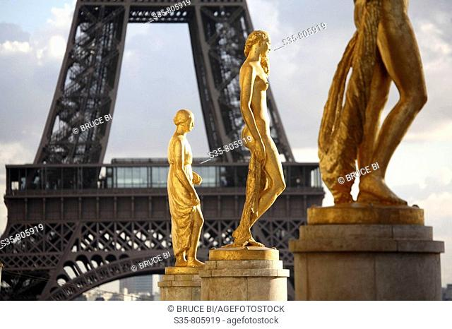 Gilded bronze statues decorating the central square of the Palais de Chailot with Eiffel Tower in background, Paris. France