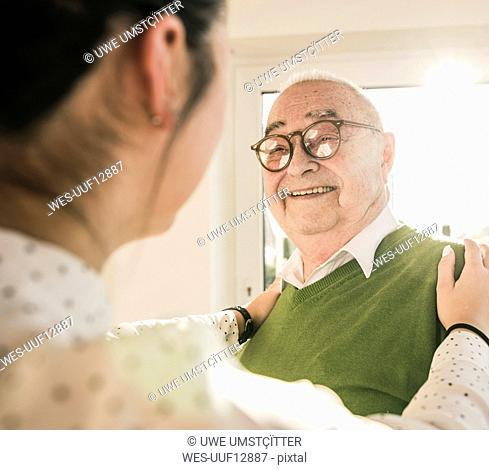 Senior man smiling at young woman